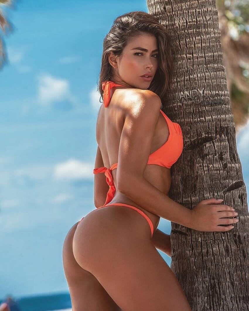 Paola Canas leaning against the tree and posing for a fitness photo shoot