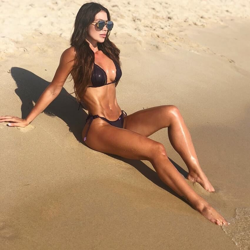 Paola Canas lying on the beach in her black bikini, soaking up the sun