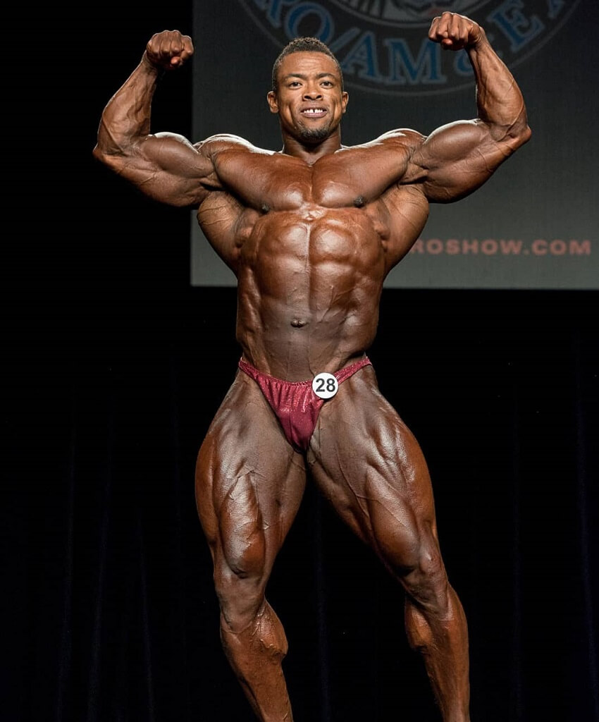 Ricardo Correia hitting a front double biceps pose on the bodybuilding stage