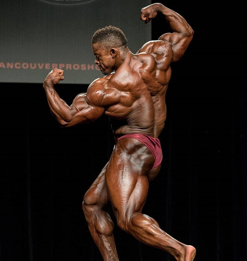 Ricardo Correia performing a pose on a bodybuilding stage, looking