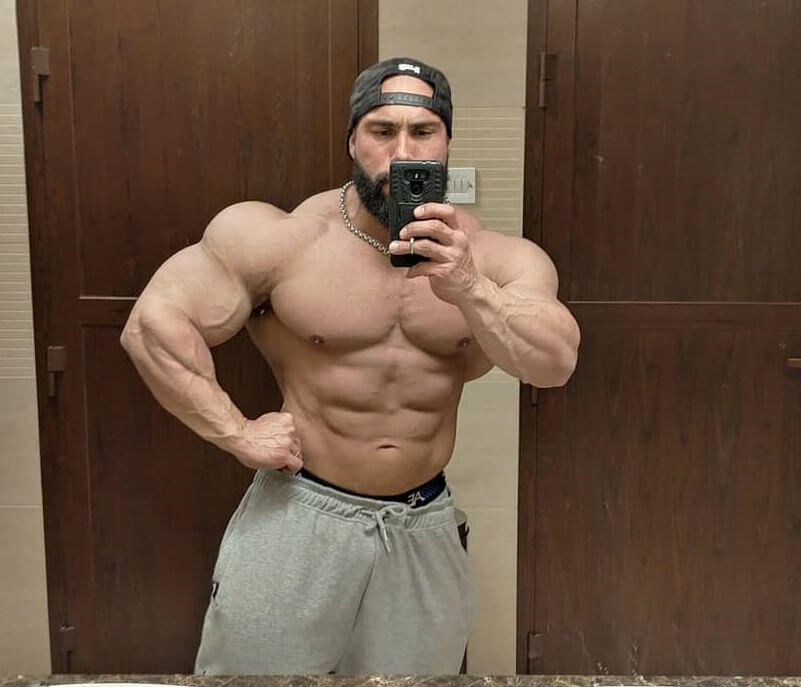 Samir Troudi taking a selfie of his huge and swole muscles in a mirror