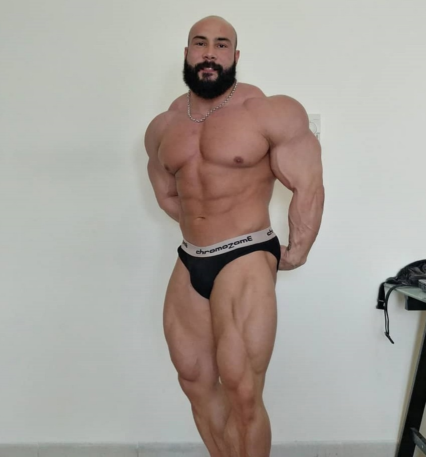 Samir Troudi flexing his huge and swole muscles for the photo