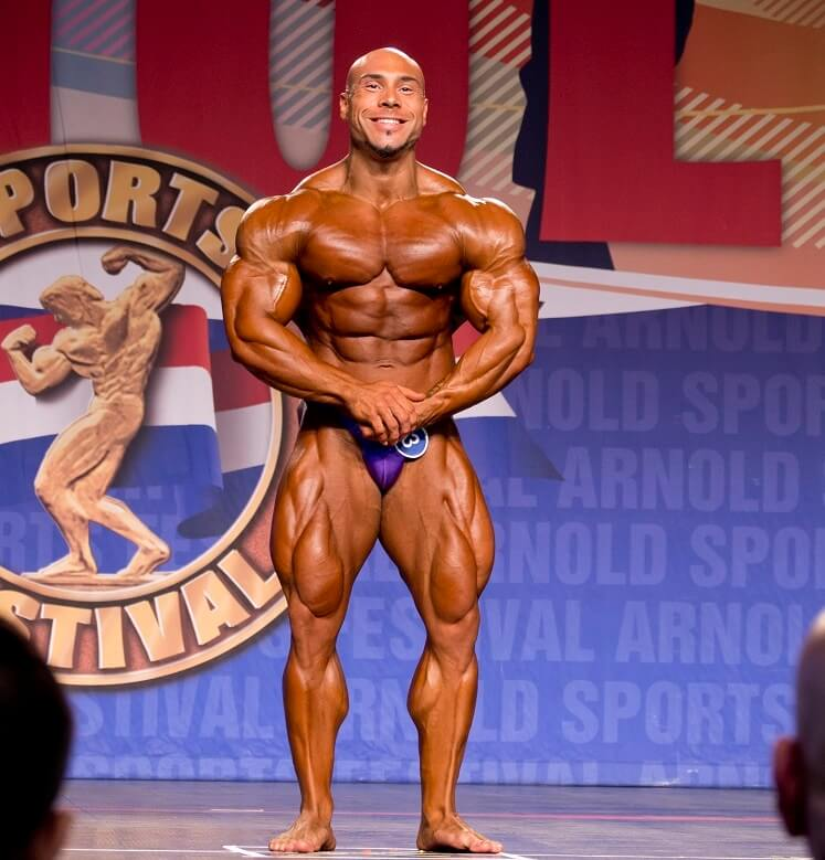 Samir Troudi flexing in his most muscular pose on the bodybuilding stage