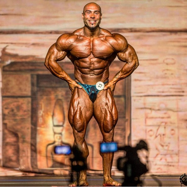 Samir Troudi flexing in a bodybuilding competition in front of cameras and an audience