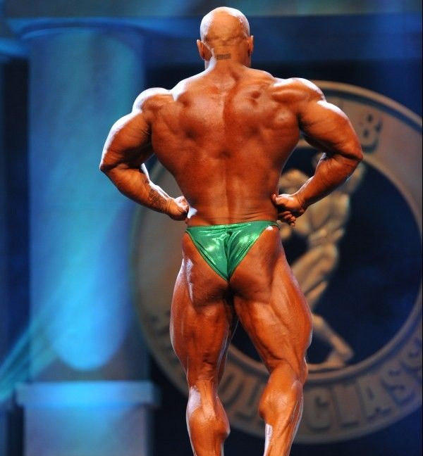 Samir Troudi performing a rear lat spread on a bodybuilding stage