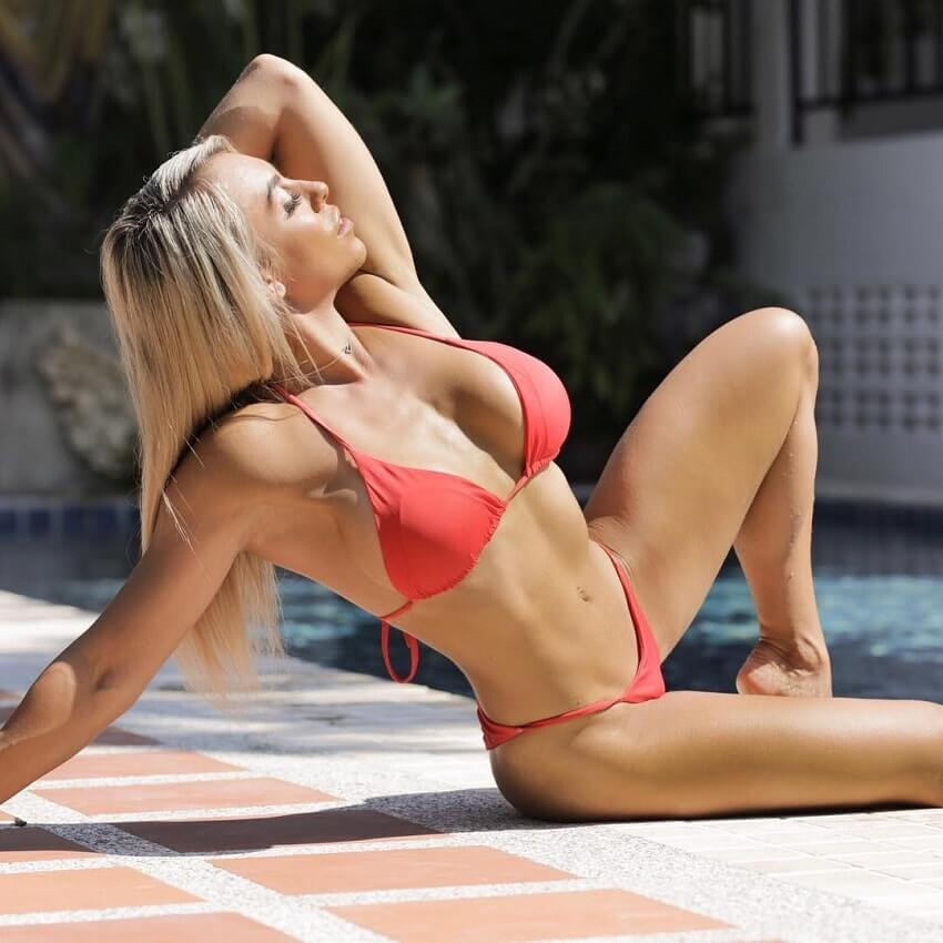 Tamara Meyer posing by the pool in a red bikini, looking fit