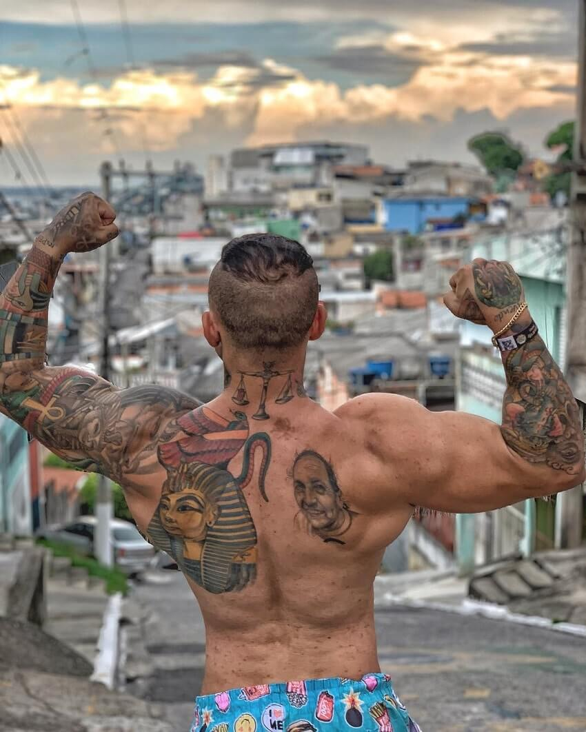 Tiago Toguro performing a bodybuilding pose shirtless on the street