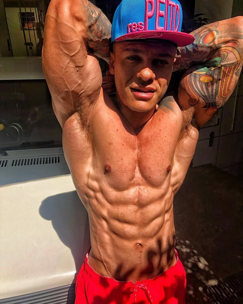 Tiago Toguro flexing his ripped and muscular abs in the photo