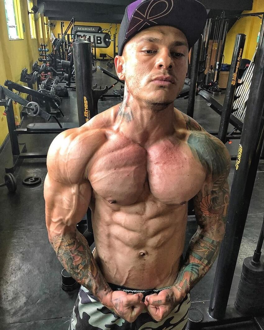 Tiago Toguro flexing shirtless in the gym