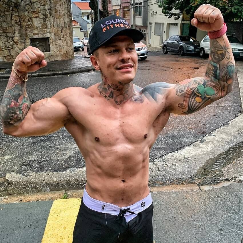 Tiago Toguro doing a shirtless front double biceps pose on the street