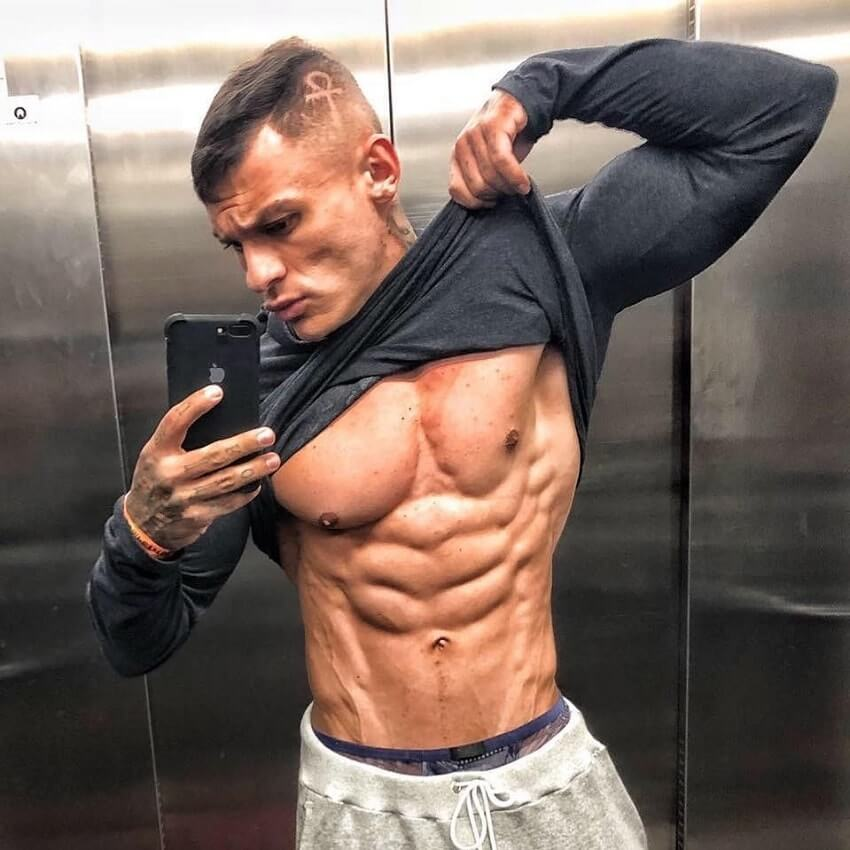 Tiago Toguro flexing his bulging abs in an elevator selfie