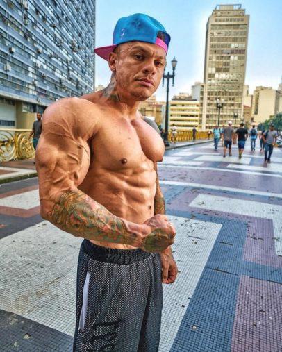 Tiago Toguro posing shirtless on the city street