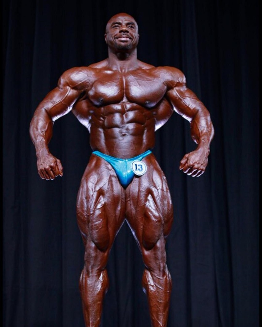 Toney Freeman posing on the bodybuilding stage looking aesthetic and huge