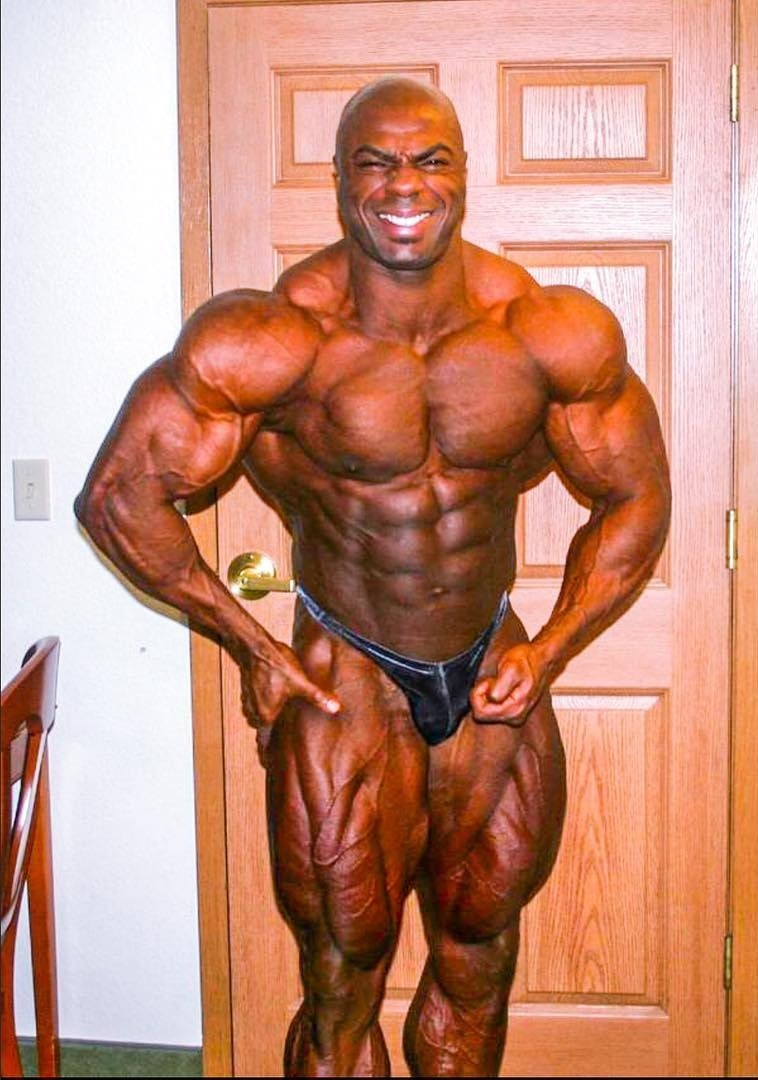 Toney Freeman posing shirtless in his house, looking ripped and huge