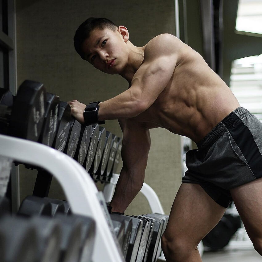 Tristyn Lee posing shirtless next to a dumbbell rack in a gym