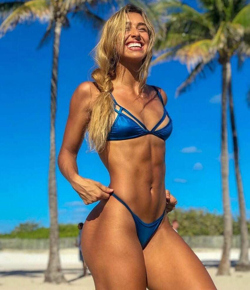 Vanesa Seco standing on the beach in a blue bikini, looking healthy and happy