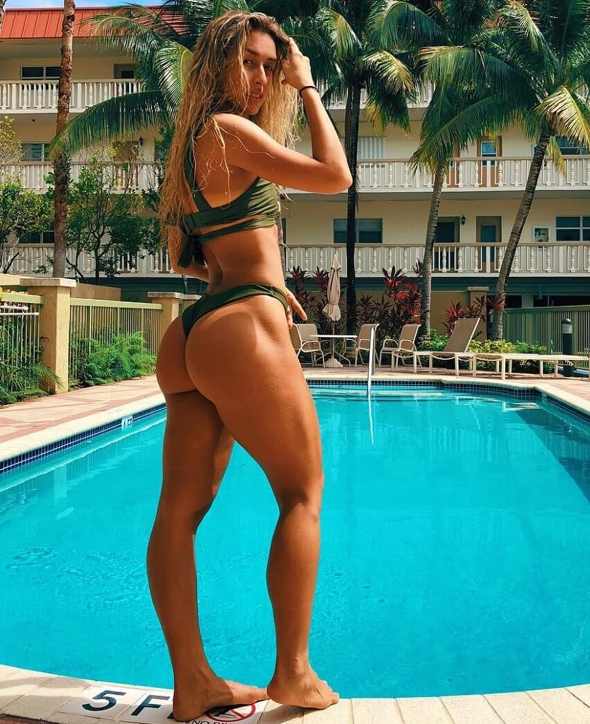 Vanesa Seco showing off her toned legs and glutes while standing by the pool
