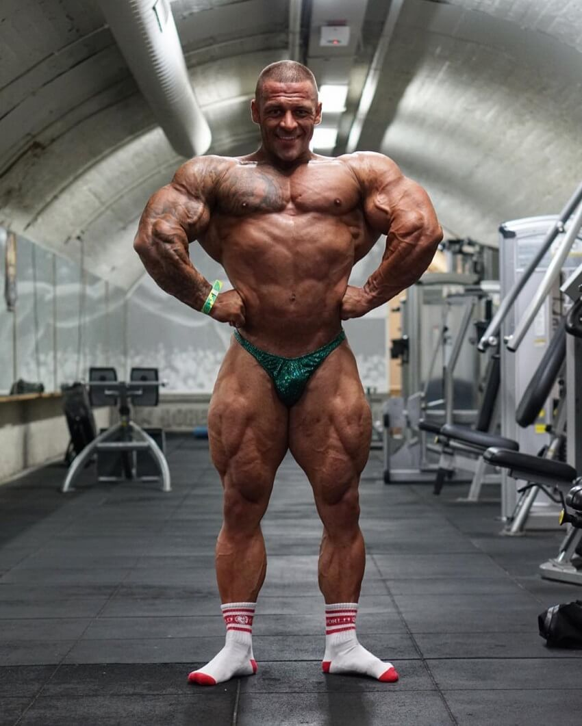 Aaron Polites performing a front lat spread shirtless in the gym