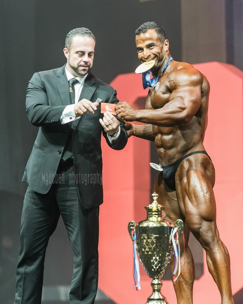 Ahmed Elsadany posing with a golden medal on the stage