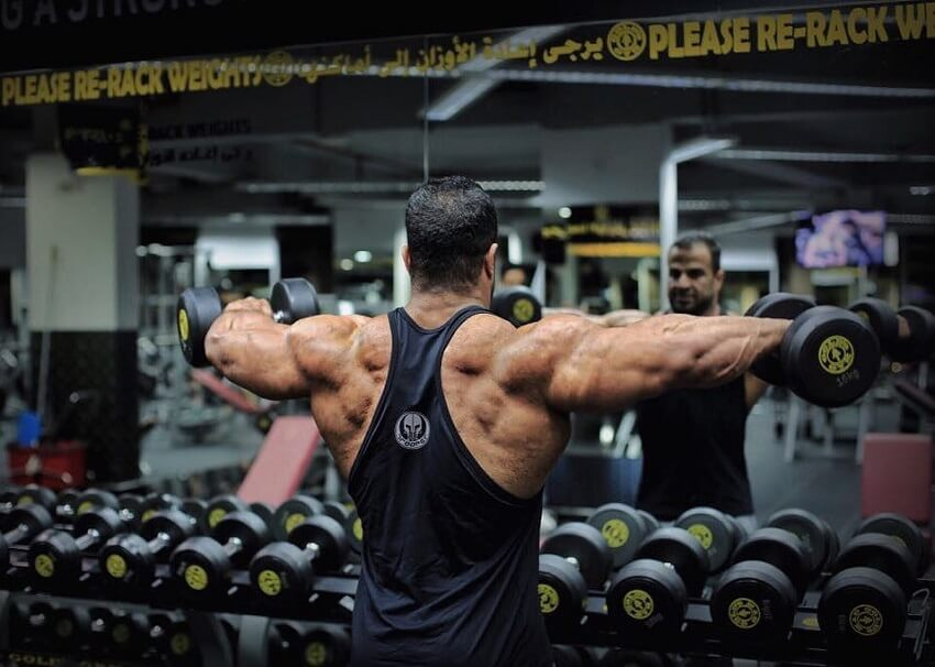 Ahmed Elsadany doing rear delt flys in the gym