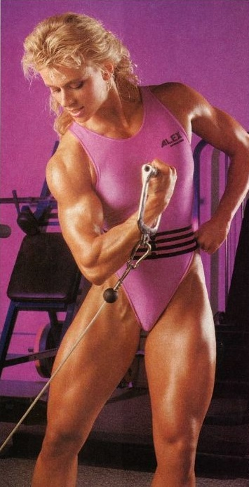 Anja Schreiner doing cable biceps curls in the gym, looking fit and healthy