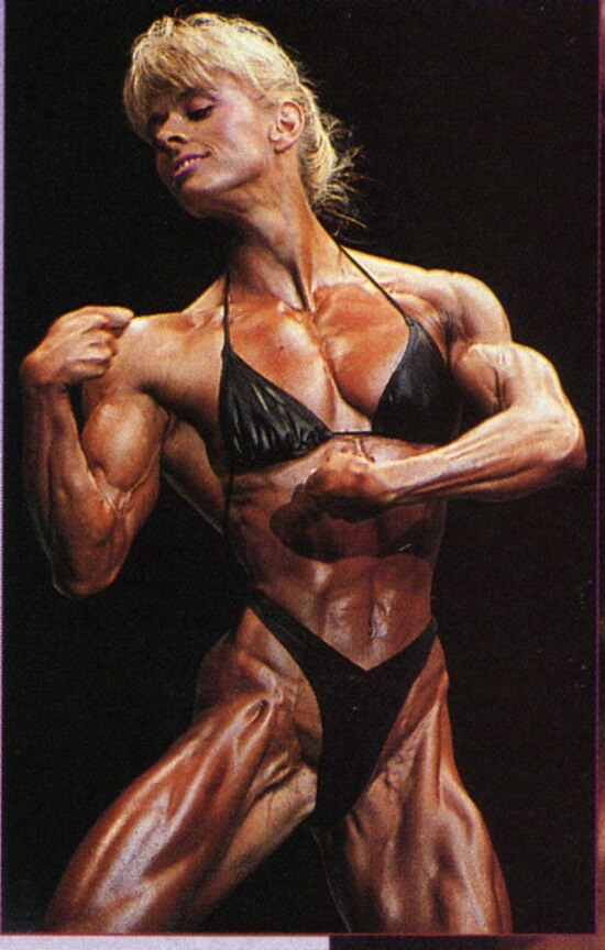 Anja Schreiner posing on the bodybuilding stage displaying her conditioned and muscular physique