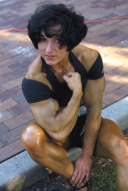 Christa Bauch flexing her arm while sitting outdoors