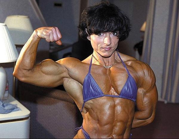 Christa Bauch flexing her biceps while wearing a bikini