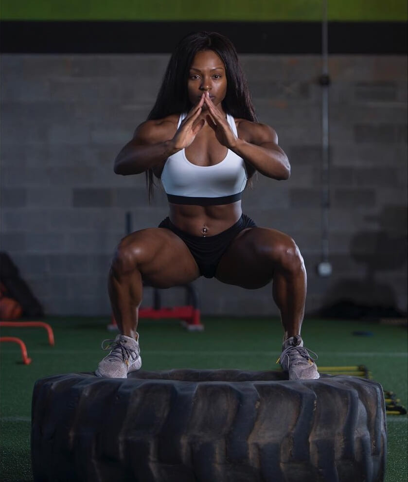 Cydney Gillon performing squat jumps on a tire