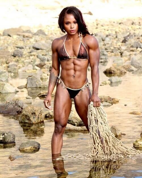 Cydney Gillon posing on the beach in a bikini looking extremely lean and aesthetic