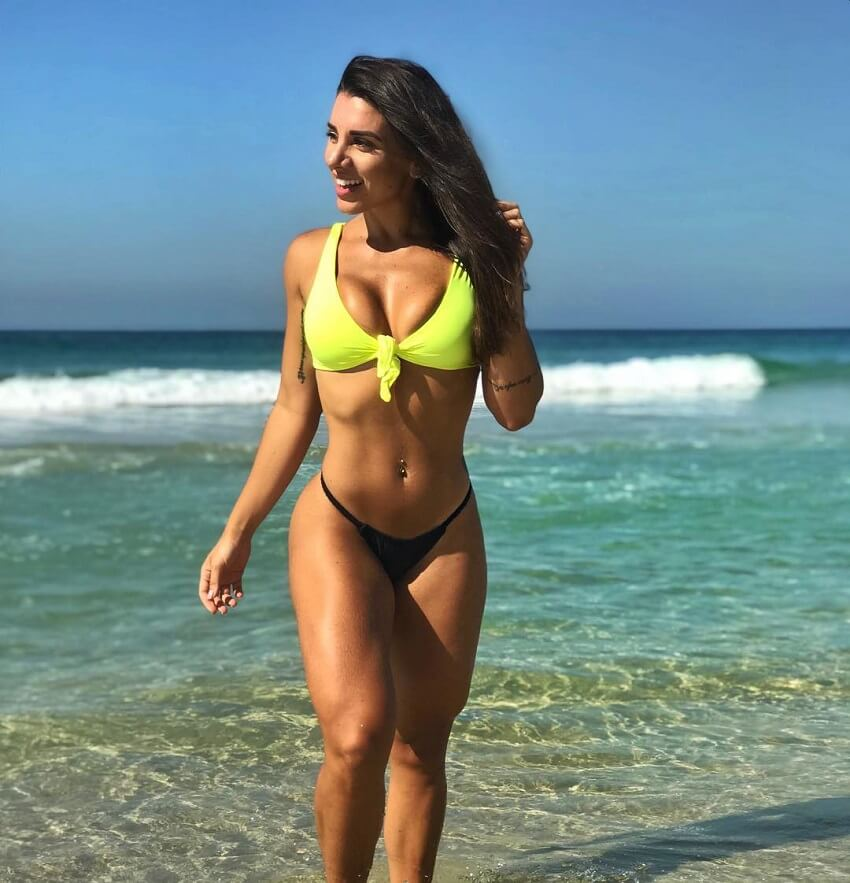 Fabriny Storck standing and smiling on the beach looking curvy and fit