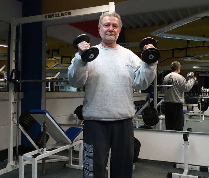Jusup Wilkosz now, posing with dumbbells in the gym