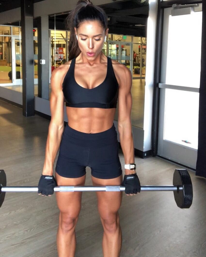 Kelsey Wells training biceps in the gym