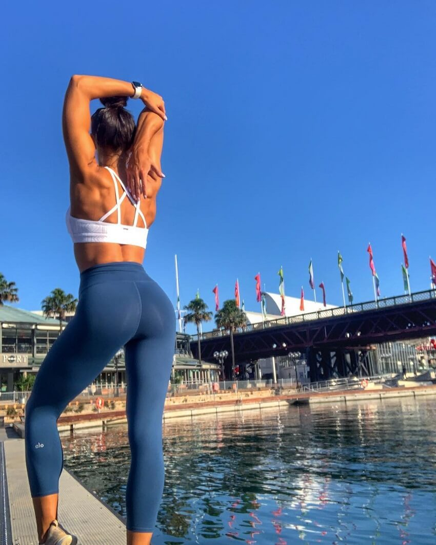 Kelsey Wells stretching outdoors, wearing blue leggings, looking curvy and awesome
