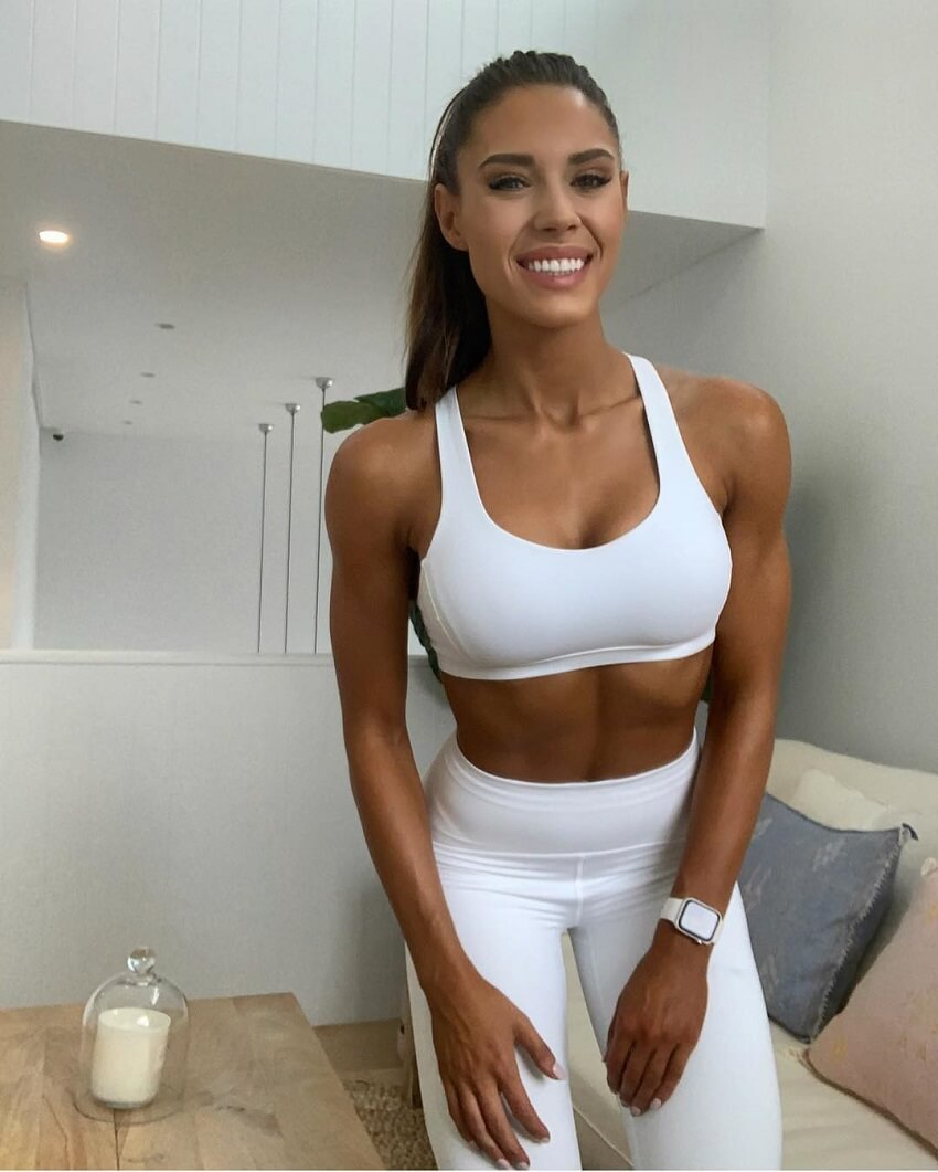 Kelsey Wells wearing white sports outfit, looking fit and lean