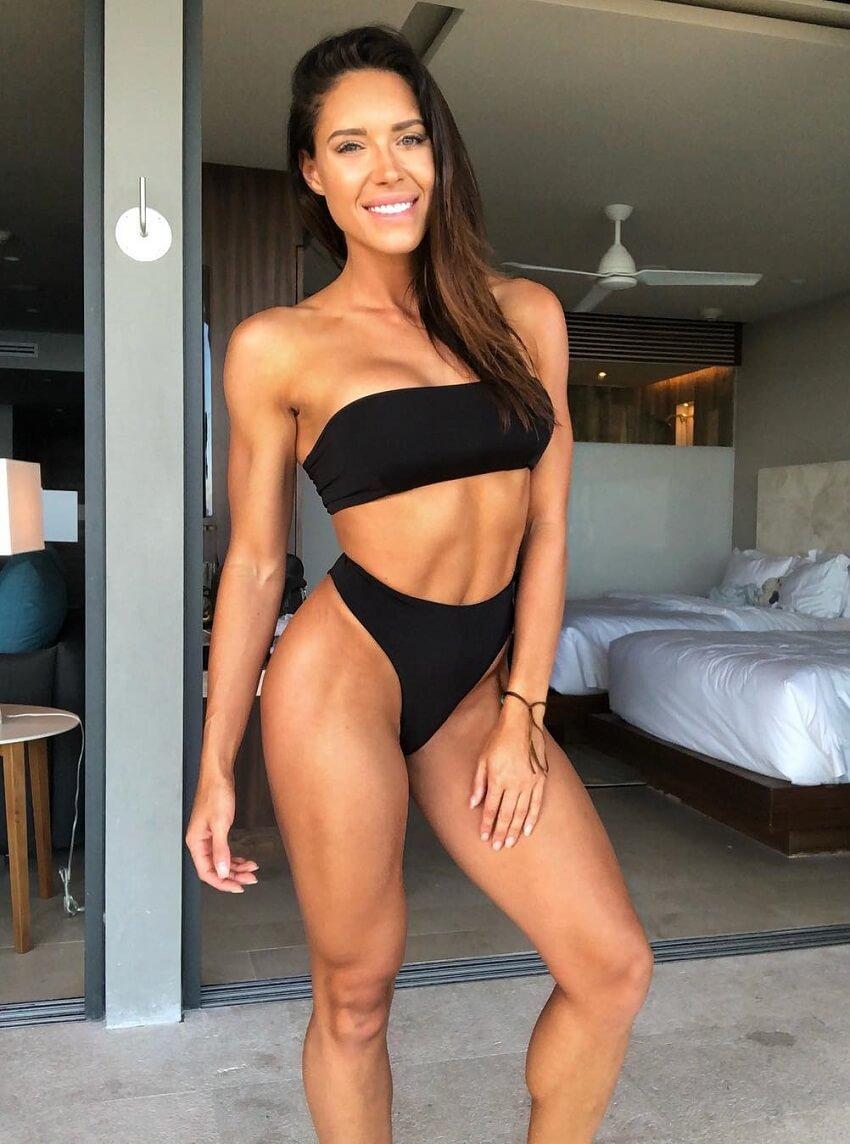 Kelsey Wells wearing a black bikini smiling for a photo