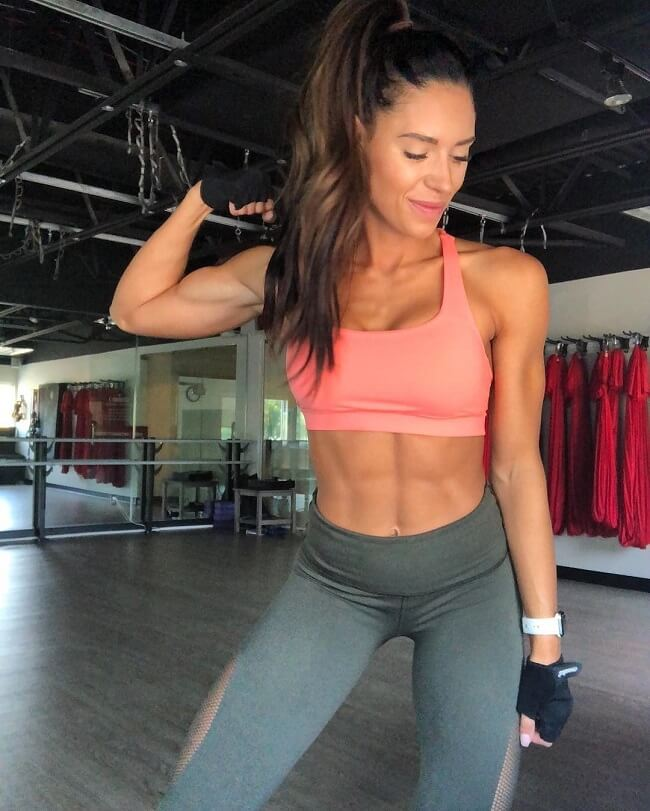 Kelsey Wells flexing her biceps and abs while smiling
