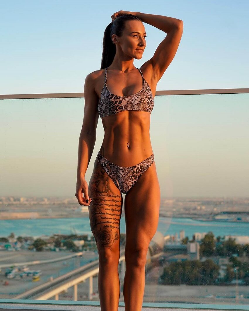 Lisa Lanceford standing on the rooftop in a bikini during a sunset, looking fit and lean