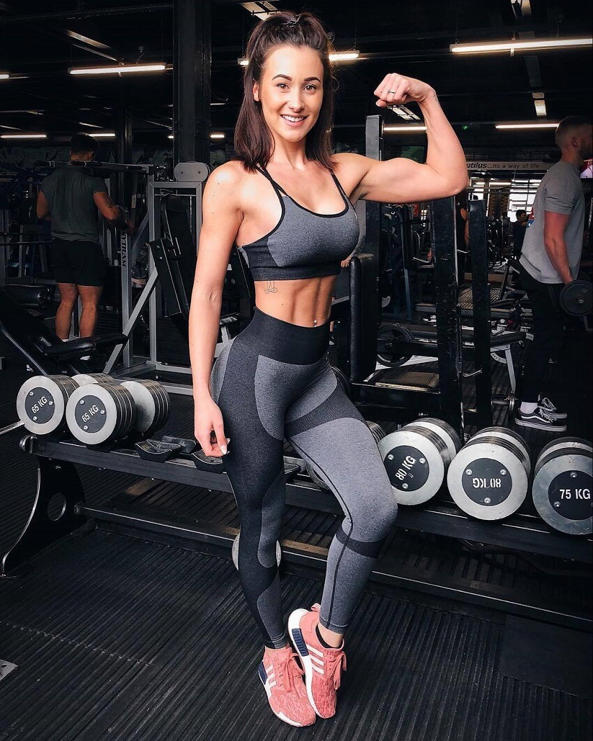 Lisa Lanceford flexing her biceps in a gym full of dumbbells