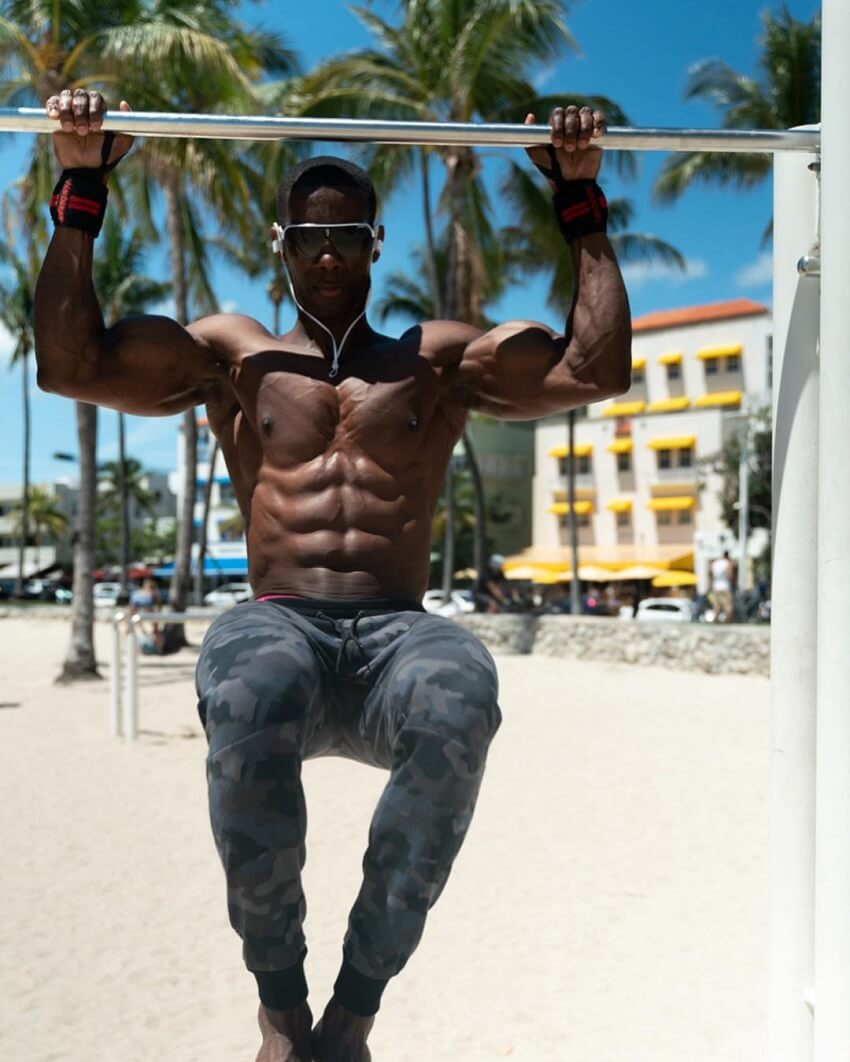 Max Philisaire doing pull ups shirtless on the Miami beach, looking extremely ripped