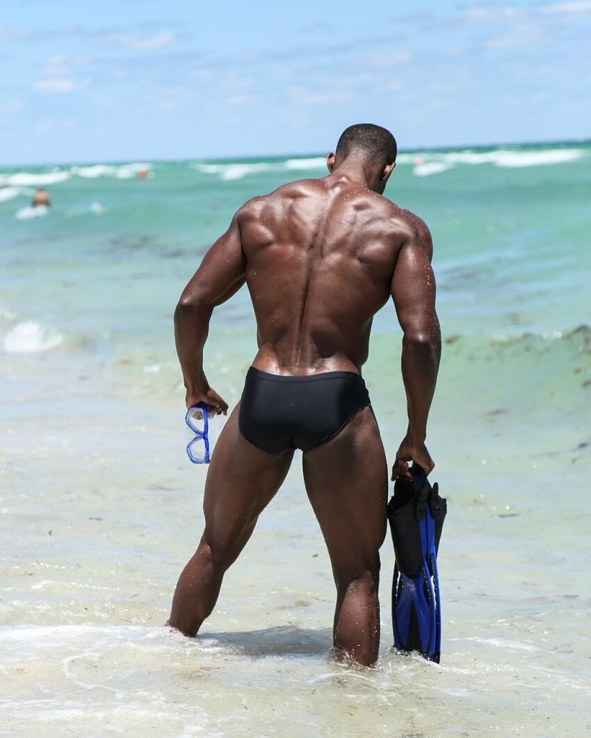 Max Philisaire standing shirtless on the beach, his lats and back looking ripped and wide