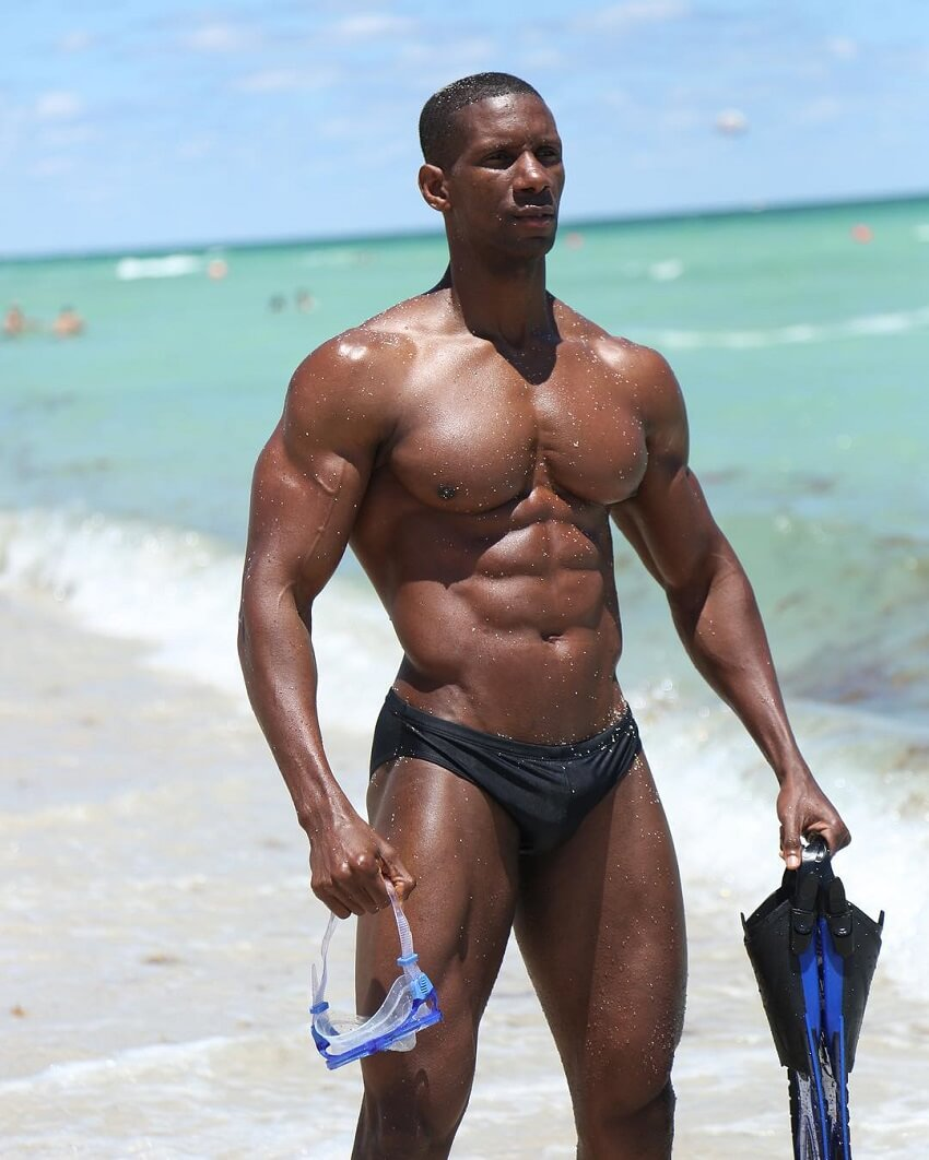 Max Philisaire standing shirtless on the beach with diving equipment and scuba fins, looking muscular and strong