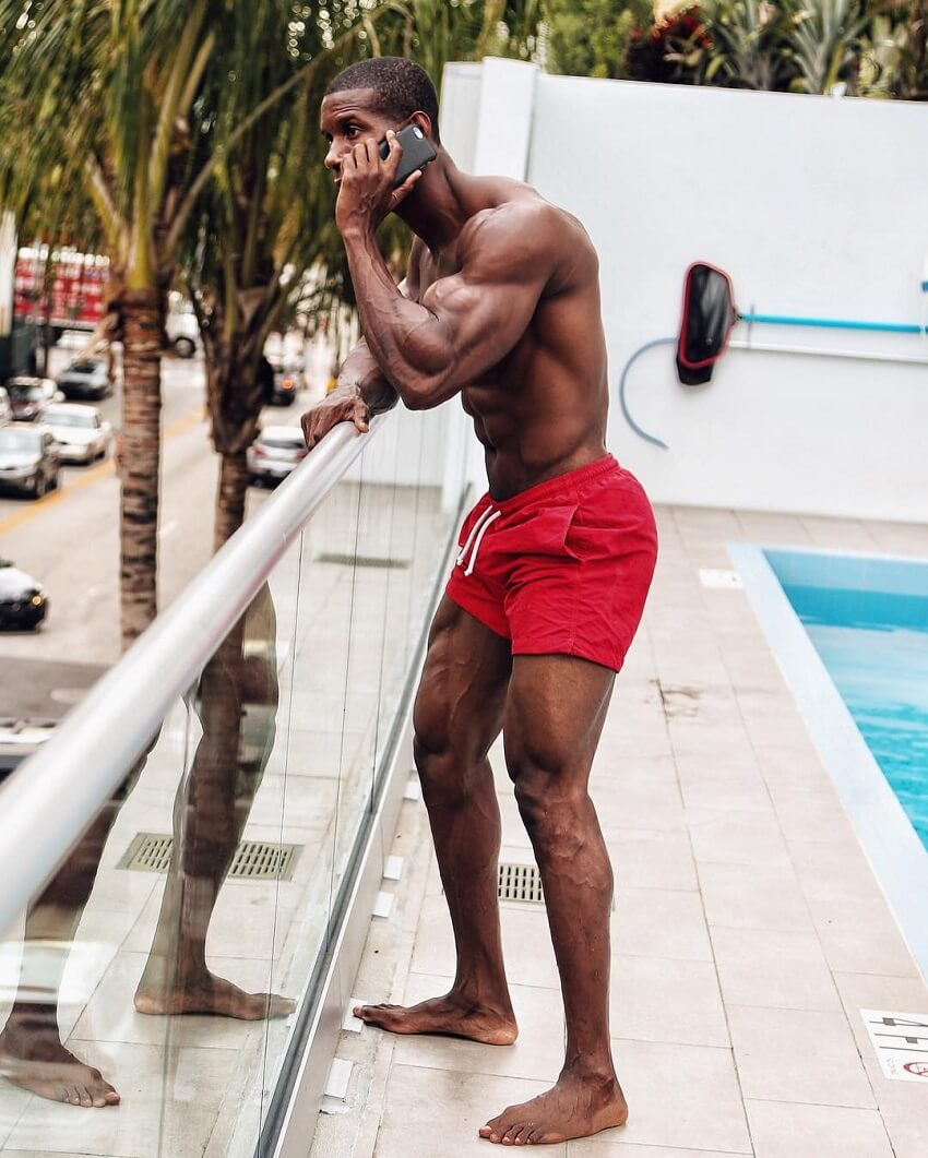 Max Philisaire standing shirtless by the pool, talking on the phone