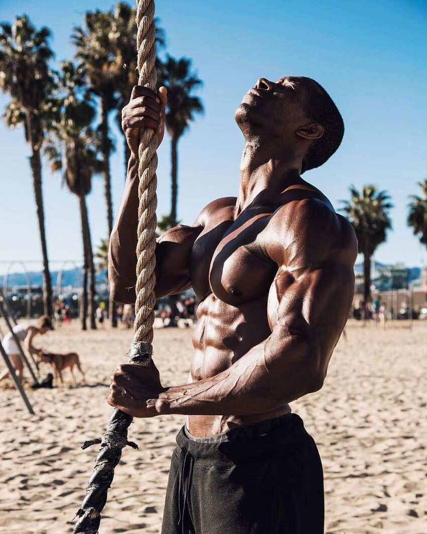 Max Philisaire standing shirtless on the beach pulling a rope and looking up