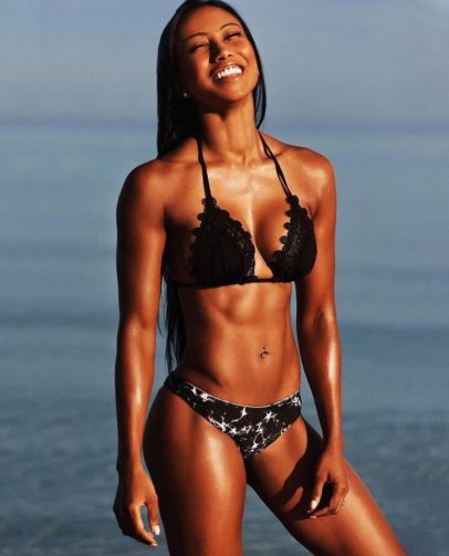 Melissa Carver smiling and posing in a bikini on the beach, looking fit and awesome