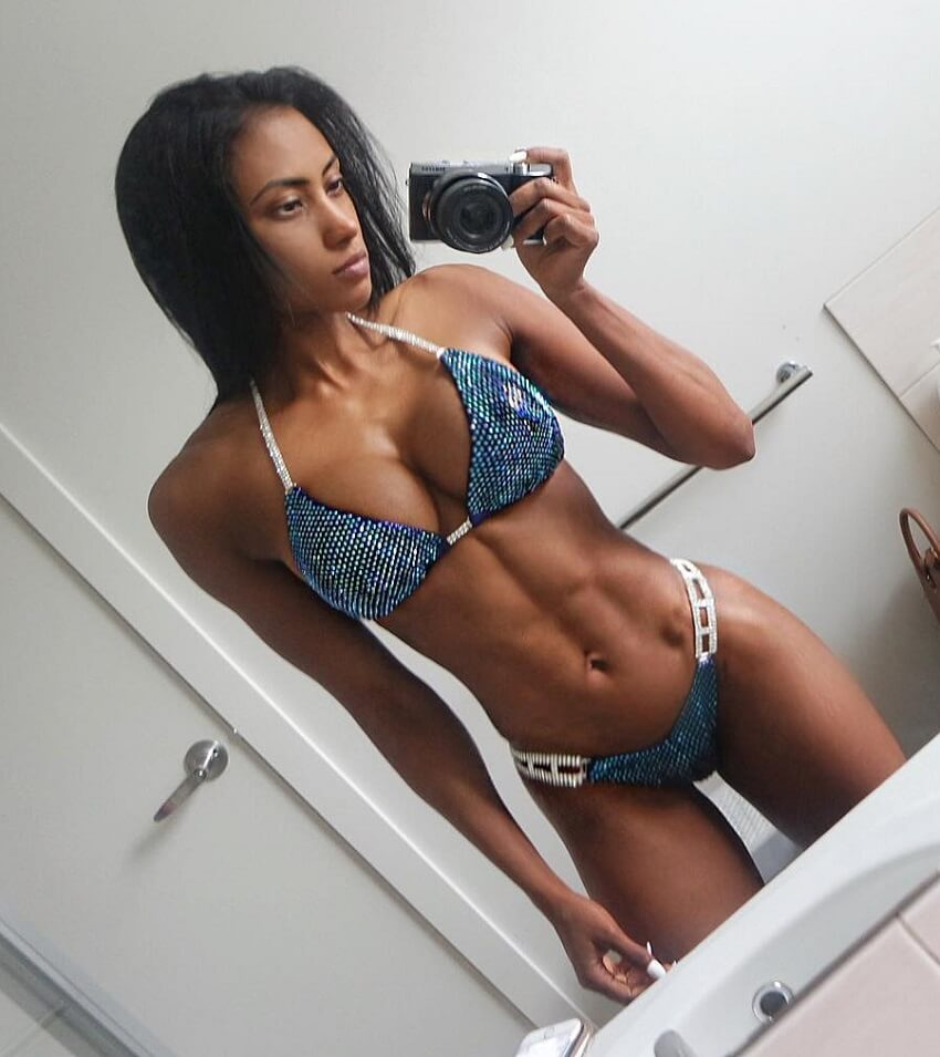 Melissa Carver taking a photo of herself in a mirror, wearing a bikini, looking fit