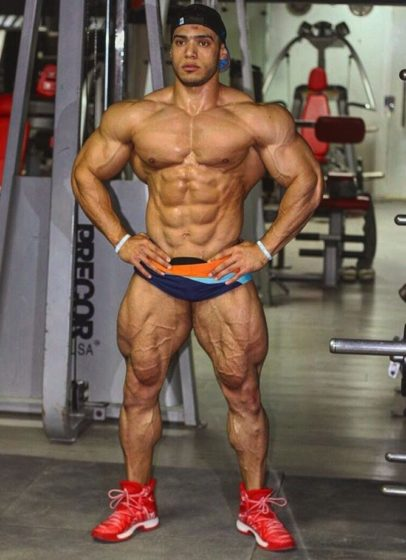 Mohammed Foda posing shirtless in the gym, looking massive and ripped