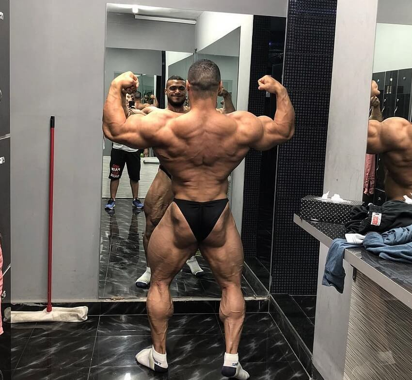 Mohammed Foda practicing back double biceps pose in front of a mirror