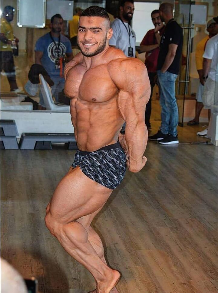 Mohammed Foda doing a shirtless side triceps pose, looking swole and ripped