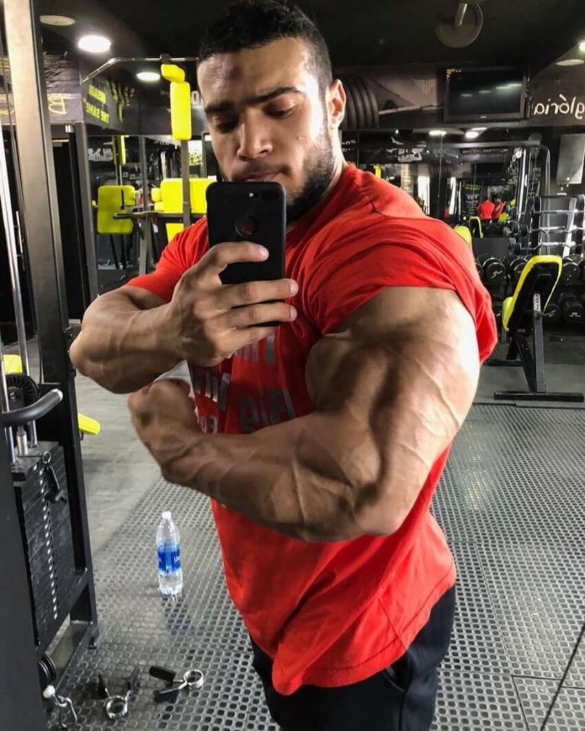 Mohammed Foda flexing his massive triceps in the mirror for a selfie